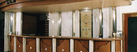 Bancone dalle linee curve realizzato in legno di rovere, con pannelli a sbalzo per inserimento di illuminazione interna.