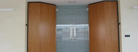 Ingresso sala riunioni con pareti in Noce nazionale biondo e ante in cristallo